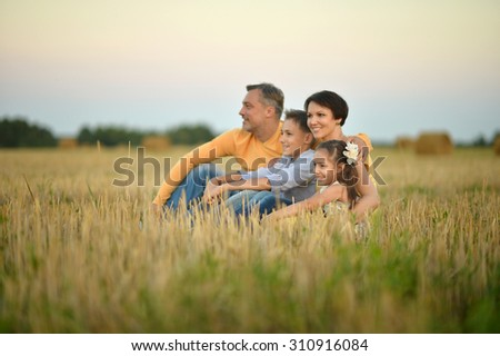 Happy family sitting  in wheat field in sunny day