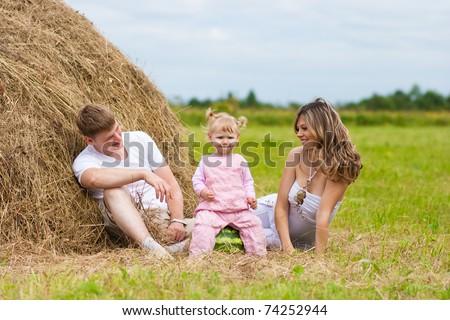 happy family sitting near haystack - stock photo