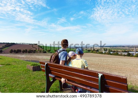 Happy family sitting on bench at meadow at sunny summer day