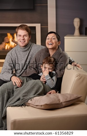 Happy family sitting on couch at home in front of fireplace, looking at camera, laughing. - stock photo