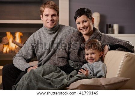 Happy family sitting on couch at home in front of fireplace, looking at camera, smiling. - stock photo