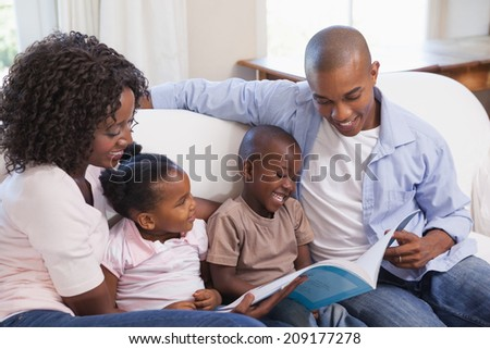 Happy family sitting on couch together reading book at home in the living room - stock photo