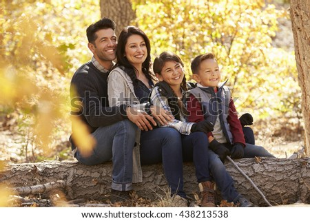 Happy family sitting on fallen tree in a forest looking away - stock photo
