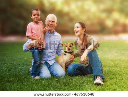 Happy family sitting on grass in yard with multi-ethnic child and dog
