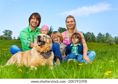 Happy family sitting on green grass with dog - stock photo