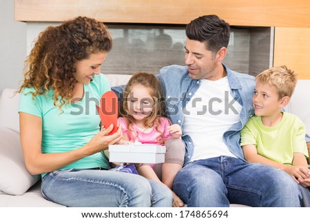 Happy family sitting on sofa celebrating a birthday at home in living room
