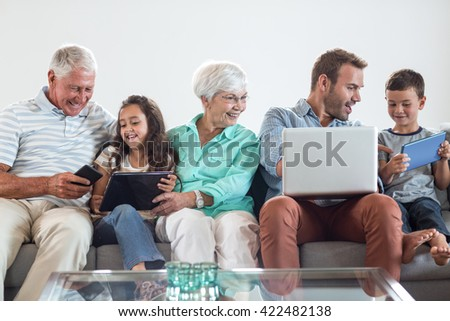 Happy family sitting on sofa using a laptop, digital, tablet, mobile phone in living room - stock photo