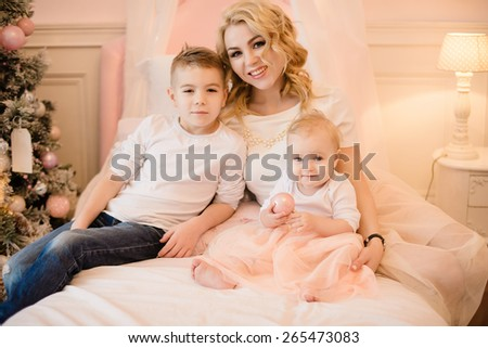 happy family sitting on the bed, mother and daughter and son