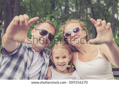 Happy family sitting on the bench in park at the day time - stock photo