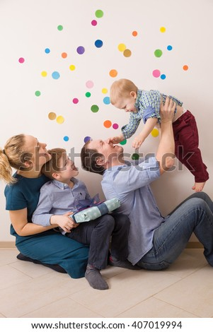 Happy family sitting on the floor at home. Mother and father with two children. Celebrating birthday. Birthday party for little toddler boy. Indoors. Mother and kid boy watching father holding baby - stock photo