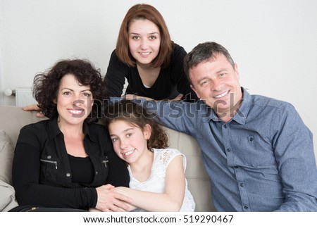 Happy family sitting on the sofa at home 2 girls and parents