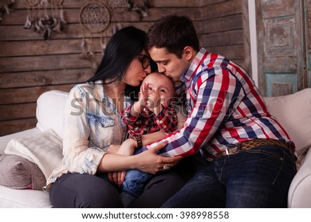 Happy family sitting on the sofa at home. Mom and dad kissing their toddler little child while him claps his hands - stock photo