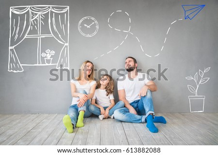 Happy family sitting on wooden floor. Father, mother and child having fun together. Moving house day, new home and design interior concept