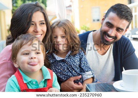 Happy family sitting together close to the pool - stock photo