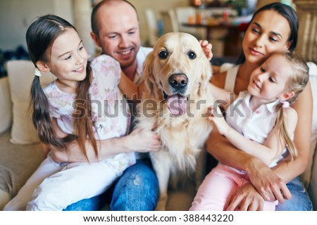 Happy family sitting together with their dog - stock photo