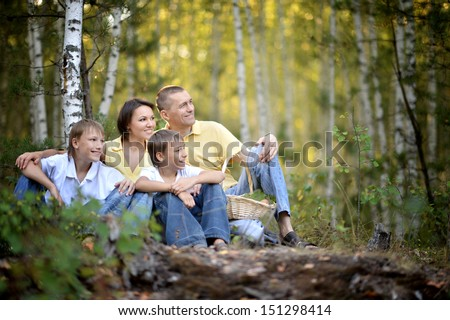 Happy family sitting under the birch in a forest - stock photo