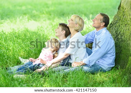 Happy family sitting under tree and looking up.