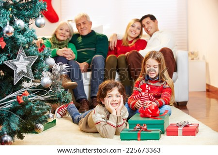 Happy family sitting with gifts at christmas tree at home