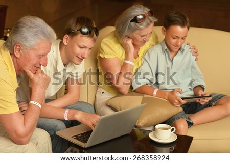 Happy family sitting with laptop and tablet computer on table