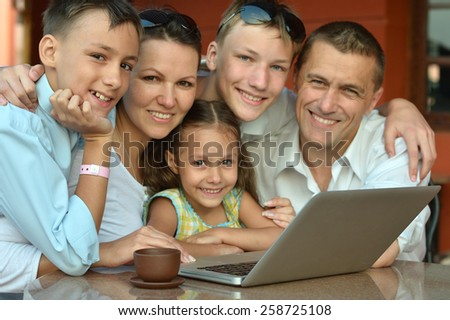 Happy family sitting with laptop on table - stock photo