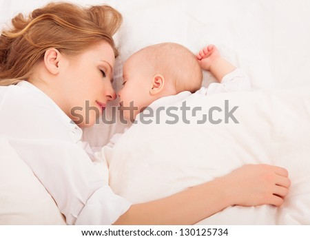 happy family sleeping together. mother embraces the newborn baby in bed - stock photo