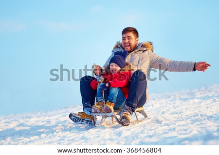 happy family sliding downhill on winter snow - stock photo