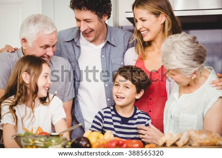 Happy family smiling and standing together in kitchen - stock photo
