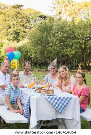 Happy family smiling at camera at birthday party outside at picnic table - stock photo