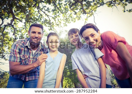 Happy family smiling at camera in the park on a sunny day