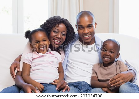 Happy family smiling at camera together at home in the living room - stock photo
