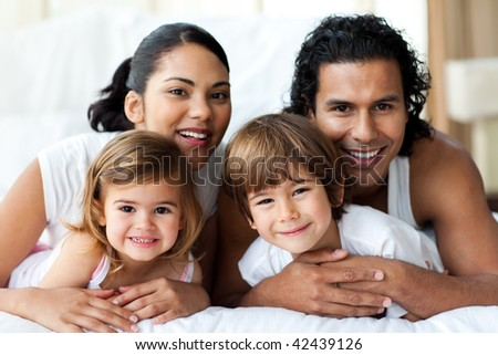 Happy family smiling at the camera in the bedroom - stock photo