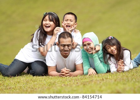 happy family smiling in a portrait of a mum and dad with their three kids