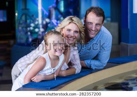 Happy family smiling to camera at the aquarium - stock photo