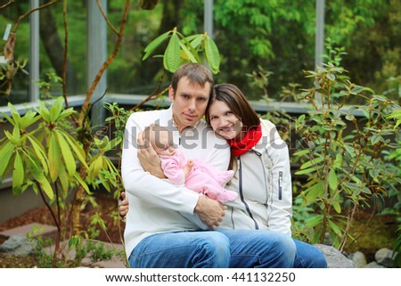 Happy family smiling together in the garden. Cute small baby in pink dress on father's hands - stock photo