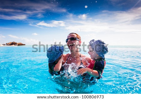 Happy family splashing in blue swimming pool on a tropical resort
