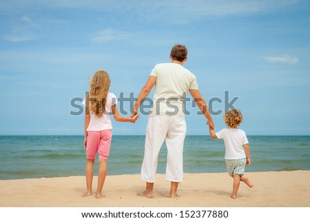 Happy family standing at the beach in the day time