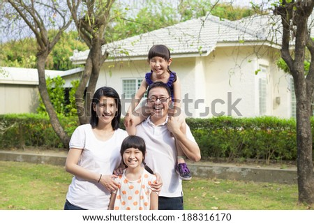 Happy family standing before their house - stock photo