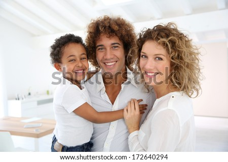 Happy family standing in brand new home - stock photo