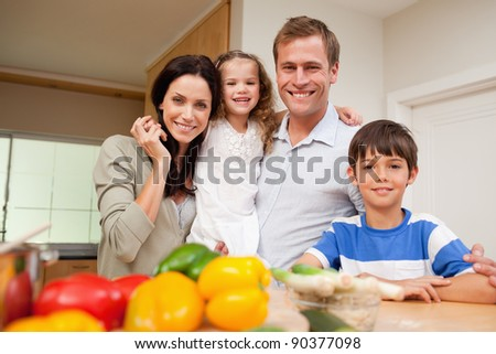 Happy family standing in the kitchen together