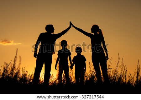 Happy family standing in the park at the sunset time.  Concept of friendly family. - stock photo