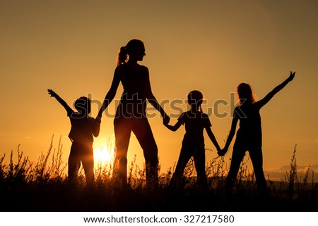 Happy family standing in the park at the sunset time.  Concept of friendly family.