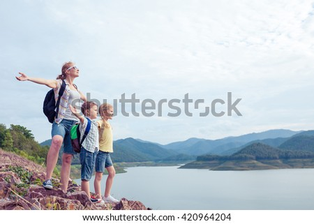 Happy family standing near the lake at the day time.  Concept of friendly family. - stock photo