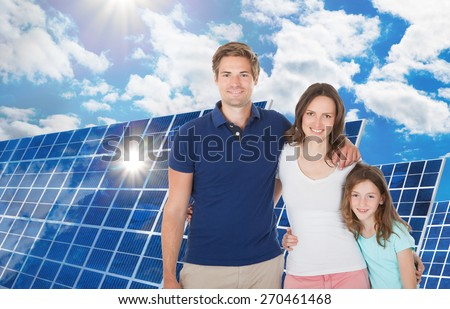 Happy Family Standing Near The Large Solar Panel - stock photo
