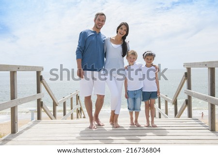 happy family  standing on a wood pontoon in front of the sea in summertime - stock photo