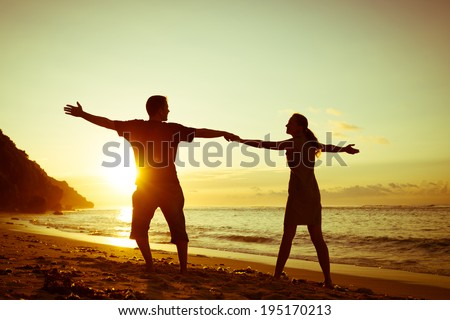 Happy family standing on the beach at the dawn time