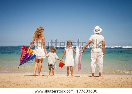 Happy family standing on the beach at the day time