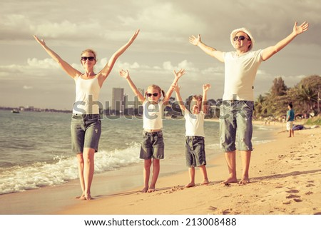 Happy family standing on the beach at the day time. - stock photo