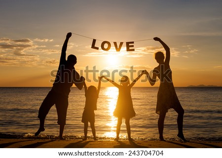 "Happy family standing on the beach at the sunset time. Parents hold in the hands  inscription ""Love"". Concept of friendly family. - stock photo"