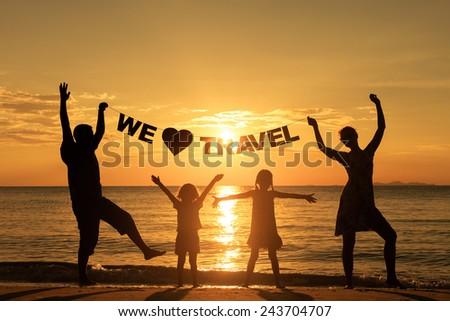 "Happy family standing on the beach at the sunset time. Parents hold in the hands  inscription ""We love travel"". Concept of friendly family."