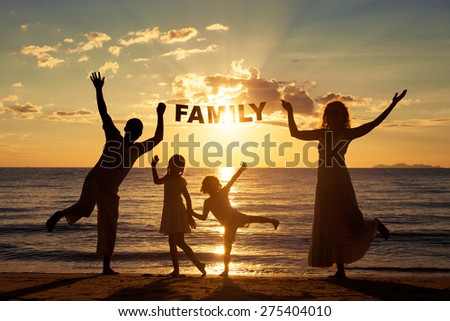 "Happy family standing on the beach at the sunset time. They keep the letters forming the word "" family"". Concept of friendly family. - stock photo"